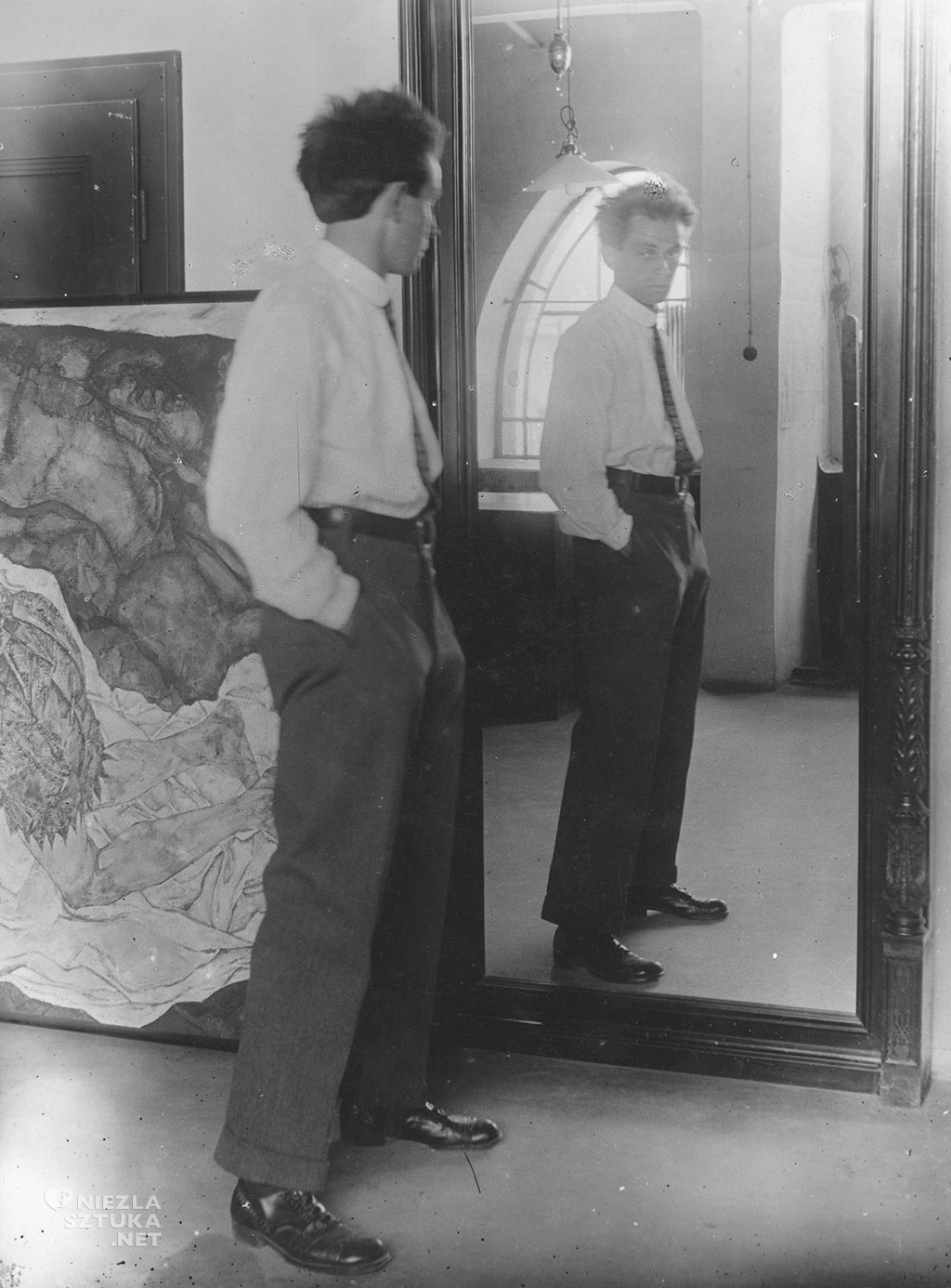 Egon Schiele, Portrait of Egon Schiele in front of his mirror in his Hietzing Atelier, in the backround the painting »Death and Girl« | 1915 Photography Leopold, Private collection